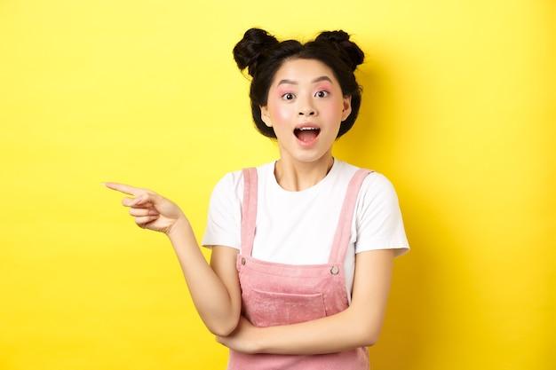興奮したアジアの10代の少女がロゴに指を置き、幸せそうに見え、広告を表示し、黄色に立っています。