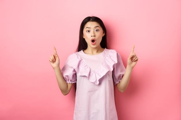 Возбужденная азиатская девушка-подросток показывает пальцами вверх, говорит