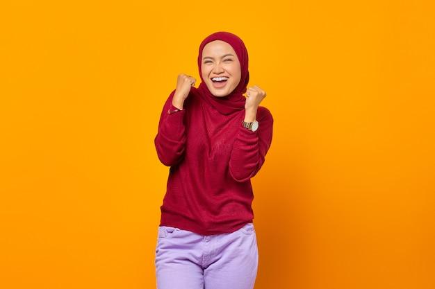 幸運を祝い、黄色の背景に勝利のジェスチャーを作る興奮したアジアの女性