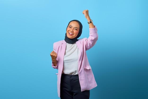 파란색 배경 위에 웃는 표정으로 성공을 축하하는 흥분된 아시아 여성