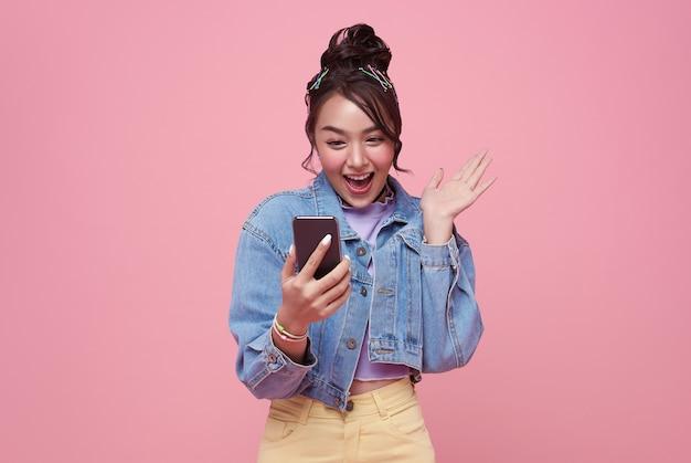 Возбужденная азиатская женщина празднует с мобильным телефоном, изолированным на розовом фоне.