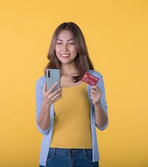 色の背景で隔離の携帯電話を見ながら興奮してクレジットカードとスマートフォンを保持している興奮したアジアの女性