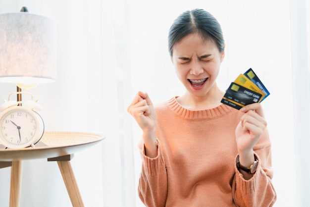 Excited asian woman holding a credit card