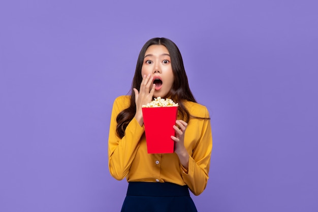 Excited asian woman holding popcorn and gasping while watching movie