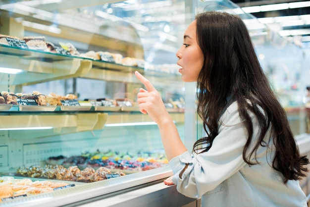 Excited asian woman pointing on dessert in pastry store