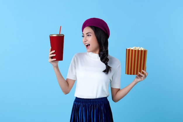 Excited asian woman watching movie film holding popcorn and cup of soda on bright blue.
