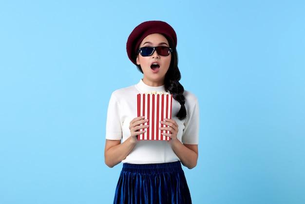 Возбужденная азиатская женщина в 3d-очках задыхается и держит попкорн во время просмотра фильма.