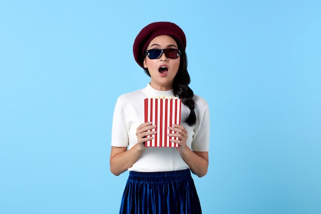 Excited asian woman wearing 3d glasses gasping and holding popcorn while watching movie.