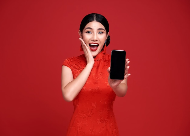 Excited asian woman wearing traditional cheongsam qipao dress showing mobile phone isolated on red wall.