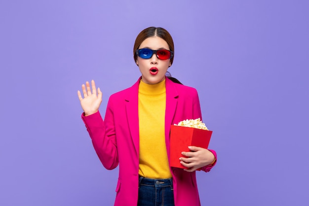 Excited asian woman with 3d glasses holding popcorn wacthing movie