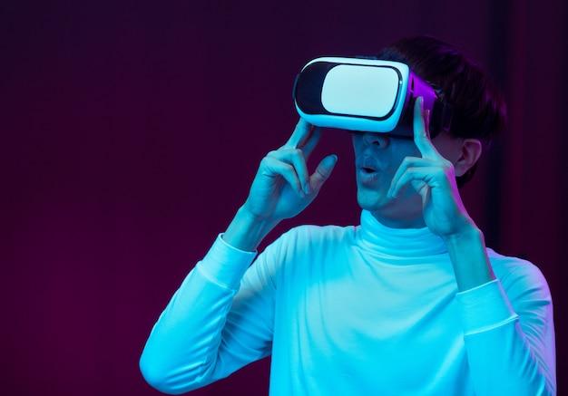 Возбужденный азиатский молодой человек в гарнитуре vr в неоновом свете, концепция технологии будущего.