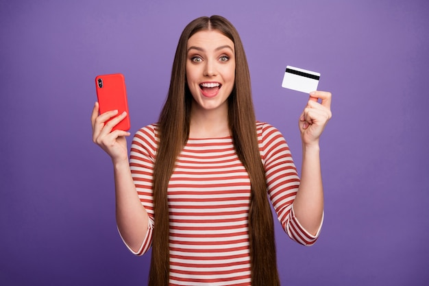 Excited astonished crazy girl use smartphone impressed easy online internet banking payment with credit card scream wow omg wear white striped jumper sweater isolated violet color wall