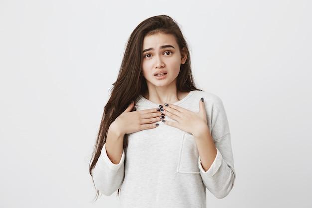 Donna carina stupita eccitata con lunghi capelli lisci scuri che mettono le mani sul seno. emozioni, sentimenti, concetto di espressione del viso