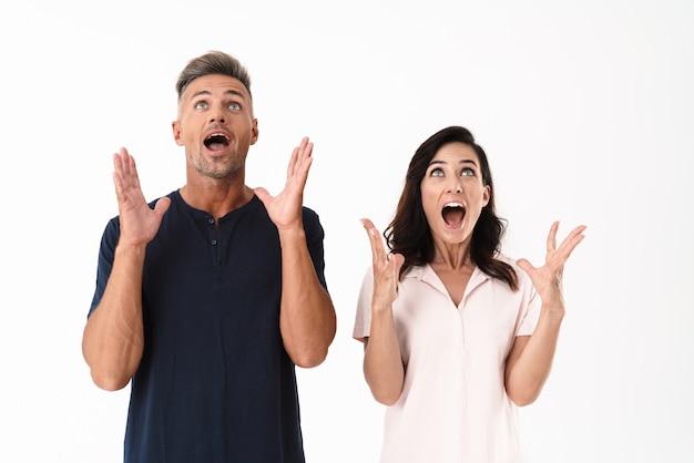 Возбужденная привлекательная пара в повседневной одежде стоит изолированно над белой стеной и празднует успех