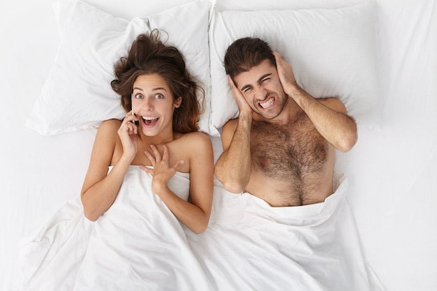 Excited attractive female talking on mobile phone, telling friend latest news and gossips whie lying in bed with her annoyed husband