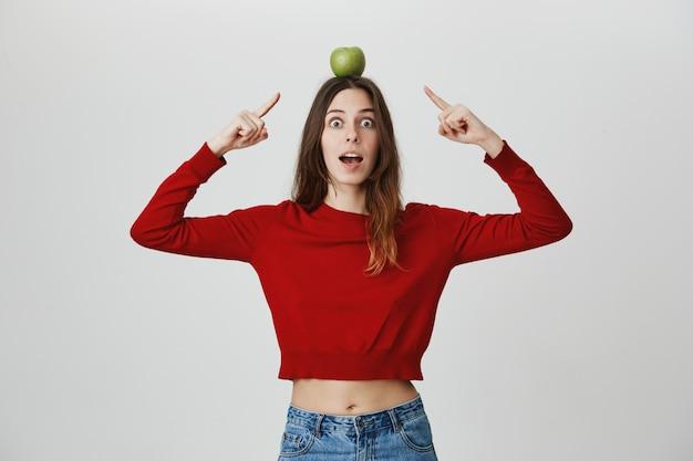 Возбужденная привлекательная девушка, указывая на цель яблоко на ее голову