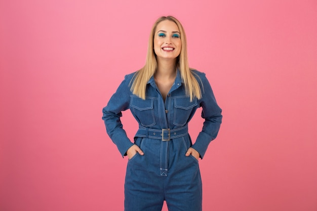 Excited attractive girl posing on pink background in denim overall fashion trend