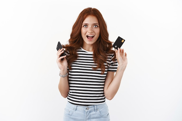 Excited attractive redhead girl raising smartphone and credit card, smiling fascinated looking upbeat, enjoy shopping online from home, input banking number, purchase outfit for prom