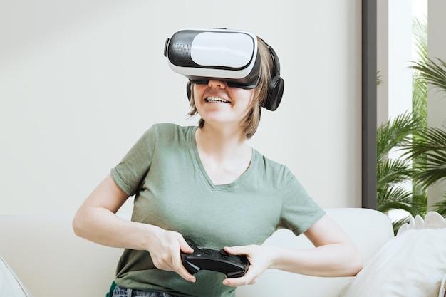 バーチャルリアリティヘッドセットまたはゴーグルを使ってゲームをし、ソファに座って、ゲームパッドコントローラーを持って、ビデオゲームをプレイする興奮した魅力的な女性。バーチャルリアリティの概念、ゲームの概念の女性