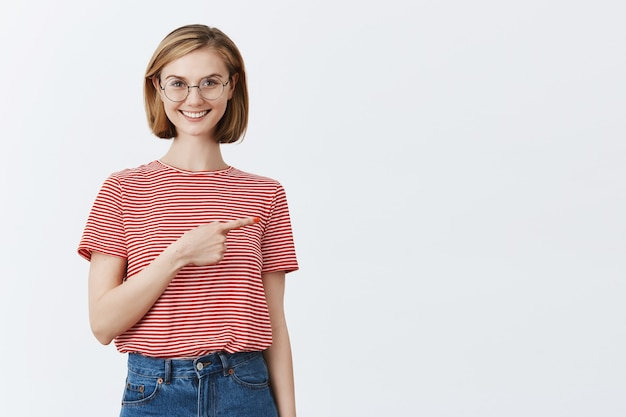 Excited attractive young girl in glasses showing way, pointing finger right at copyspace