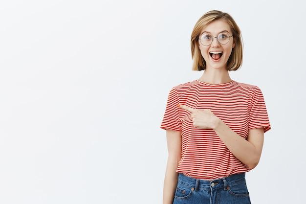 コピースペースで左の指を指して、道を示す眼鏡で興奮した魅力的な若い女の子