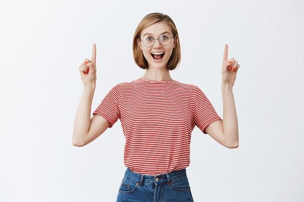 コピースペースで指を上に向けて、道を示している眼鏡の興奮した魅力的な若い女の子