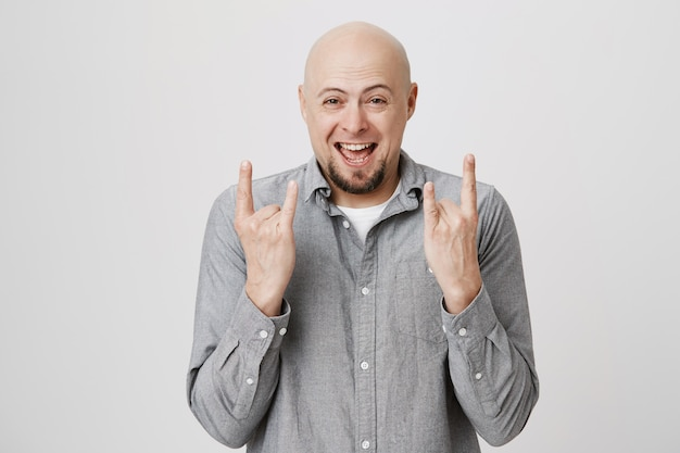 Excited bald guy smiling, showing heavy metal gesture