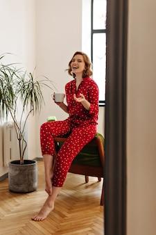一杯のコーヒーを保持しているパジャマで興奮した裸足の女性。お茶を飲み、家で笑っているうれしそうな女性の全身像。