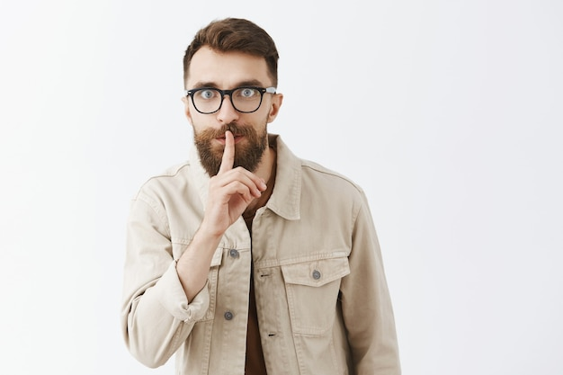 Eccitato uomo barbuto barbuto in bicchieri in posa contro il muro bianco