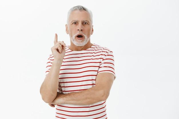 Nonno barbuto eccitato che alza il dito indice, ha un'idea, un suggerimento