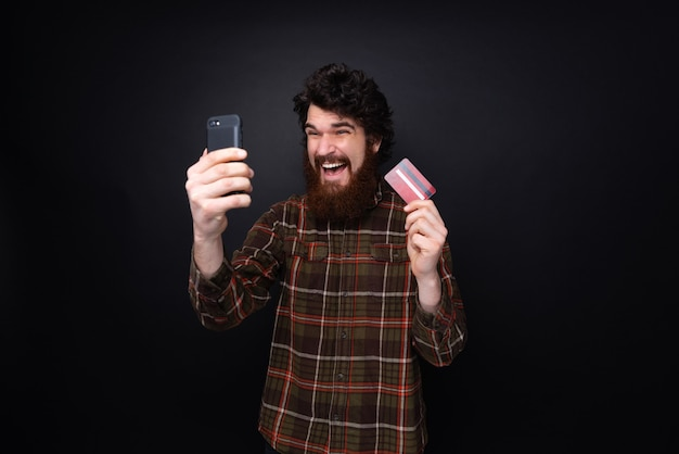 휴대폰과 신용카드를 들고 어두운 벽 배경 위에 서 있는 흥분한 수염 난 남자