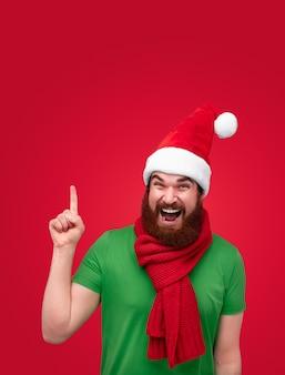 上向きのクリスマス帽子の興奮したひげを生やした男