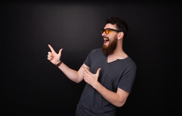 興奮したあごひげを生やした男が指で突っつい、暗い背景の上で叫んでいる