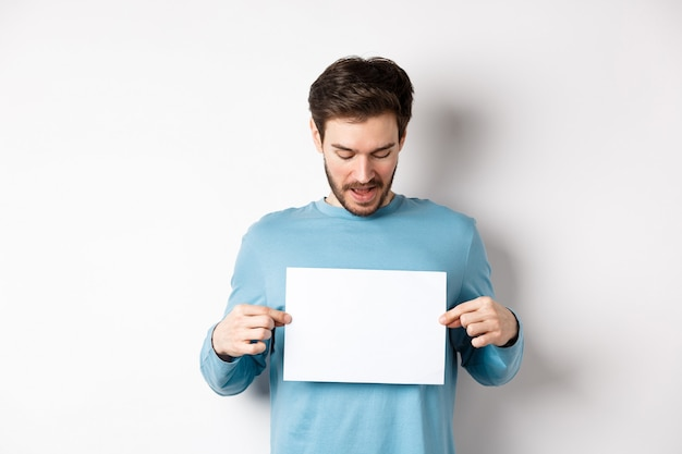Excited bearded guy reading banner on blank piece of paper, showing logo, standing over white background