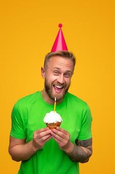 Взволнованный бородатый парень с кексом на день рождения