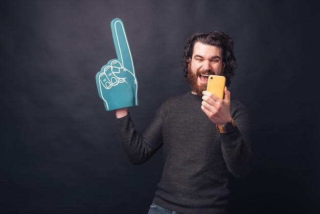 Взволнованный бородатый красавец показывает перчаткой вентилятора и смотрит на желтый смартфон