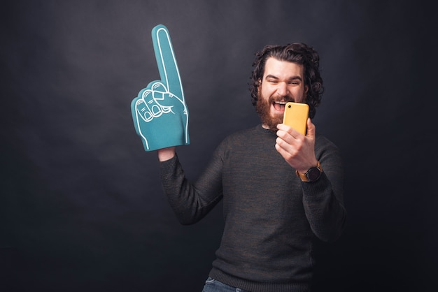 Excited bearded handsome man pointing with fan glove and looking at yellow smartphone