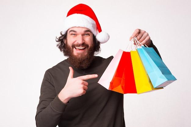 Взволнованный бородатый мужчина-хипстер указывает на пакеты, которые он купил на рождество.