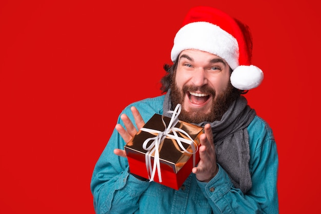 Excited bearded man holding a small holiday gift,  wearing a santa hat