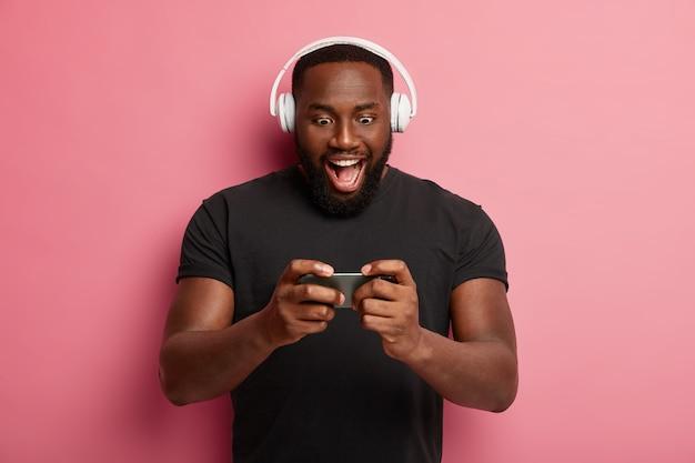 흥분된 수염 난 남자가 현대 스마트 폰을 수평으로 잡고, 온라인 게임을하고, heeadset을 사용하고, 가제트 화면에 갇히고, 검은 색 티셔츠를 입고, 혼자서 재미를 느낍니다.