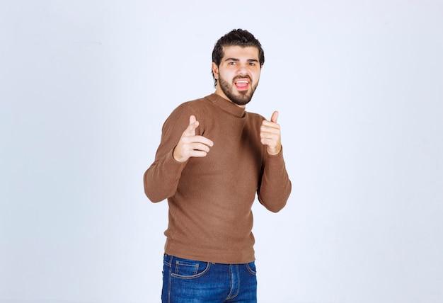 흰색 배경에 고립 된 카메라에서 손가락을 가리키는 갈색 스웨터에 수염 된 남자를 흥분. 고품질 사진