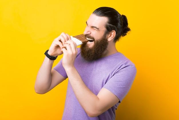興奮したひげを生やした男は、黄色の背景の上にチョコレートのバーを噛んでいます。