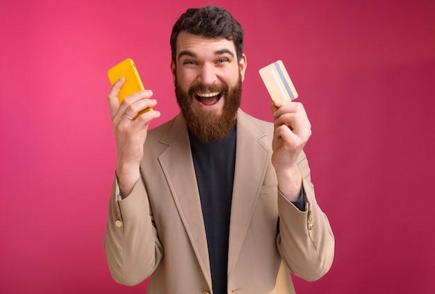 興奮したひげを生やした男はピンクの電話とカードを持っています。