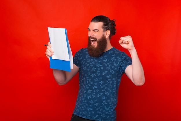Возбужденный бородатый мужчина смотрит на какие-то бумаги, делает победный жест и кричит.