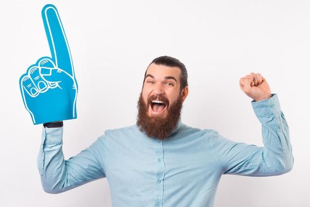 흥분된 수염 난 남자가 거품 팬 장갑을 끼고 승자 제스처를 만들고 있습니다.