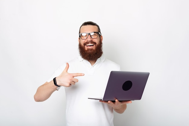 흥분된 수염 난된 남자가 흰색 배경 위에 자신의 노트북을 가리키고 있습니다.