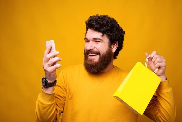 Возбужденный бородатый мужчина делает покупки в интернете, держа бумажный пакет в телефоне.