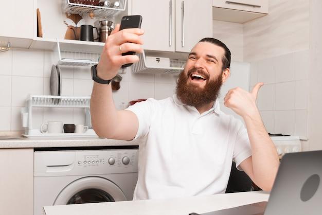 Взволнованный бородатый мужчина показывает жест и делает селфи, работая на кухне за своим ноутбуком.