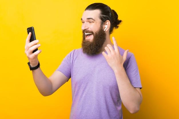 흥분된 수염 난 남자가 이어폰과 전화를 사용하고 있습니다.