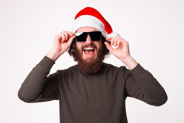 흥분한 수염 난 남자가 크리스마스 모자와 선글라스를 쓰고 있습니다.